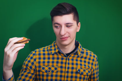 A portrait of a hungry man looking at big hamburger